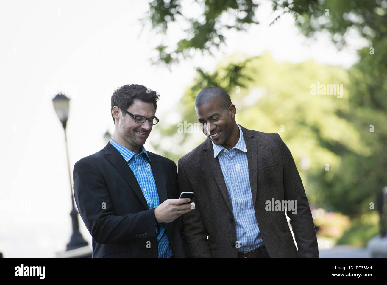 Two men walking side by side one showing the other his smart phone - Stock Image