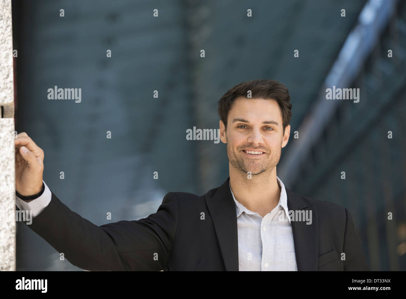 A man in a black jacket and open collared shirt - Stock Image