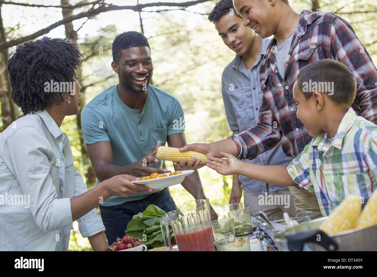 A family picnic in a shady woodland Adults and children around a table handing around plates and food - Stock Image