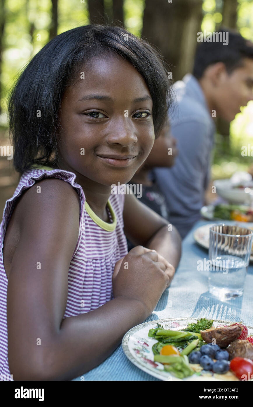 A young girl seated at the table - Stock Image