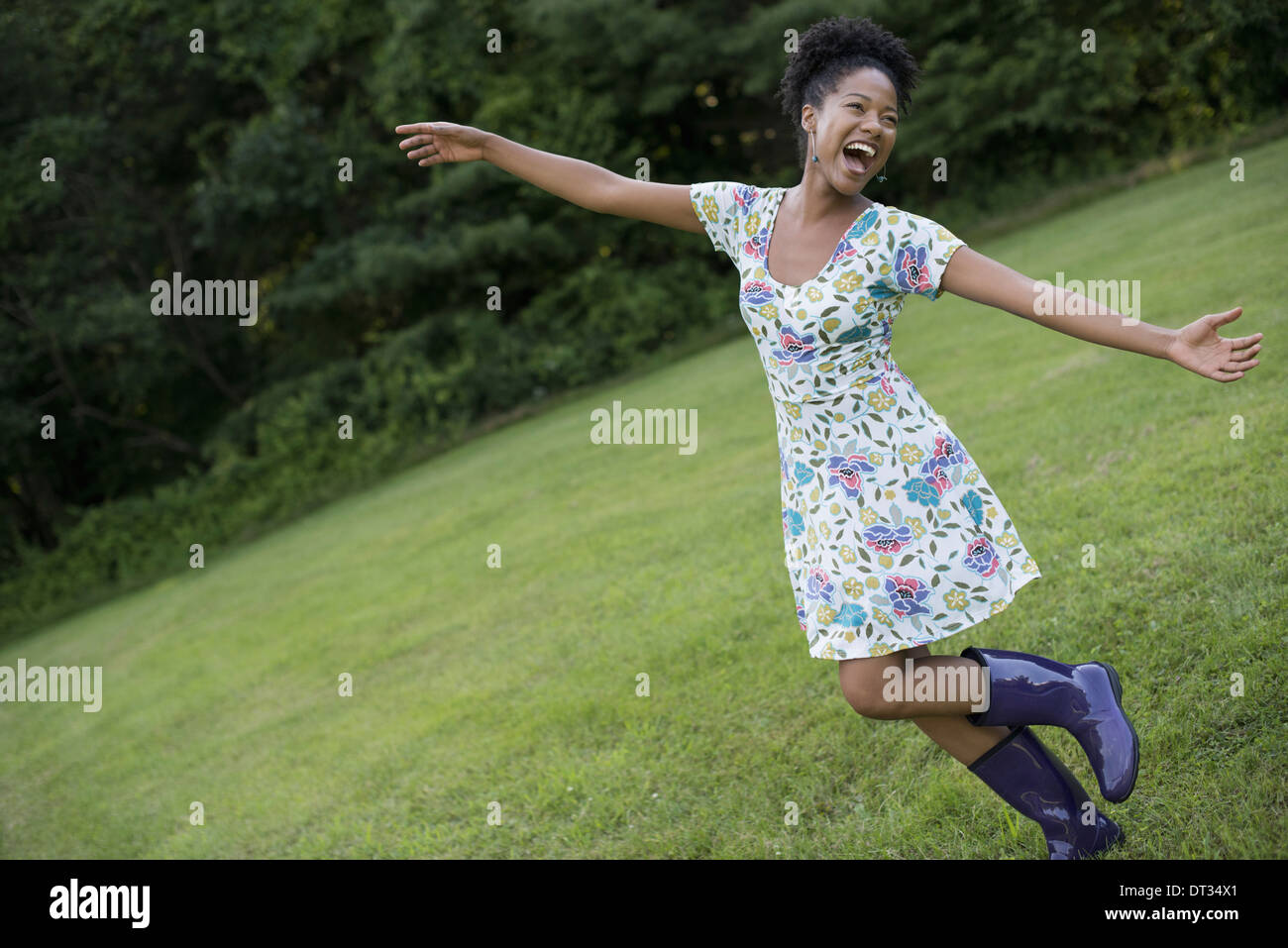 A young woman in a summer dress with her arms outstretched celebrating freedom - Stock Image