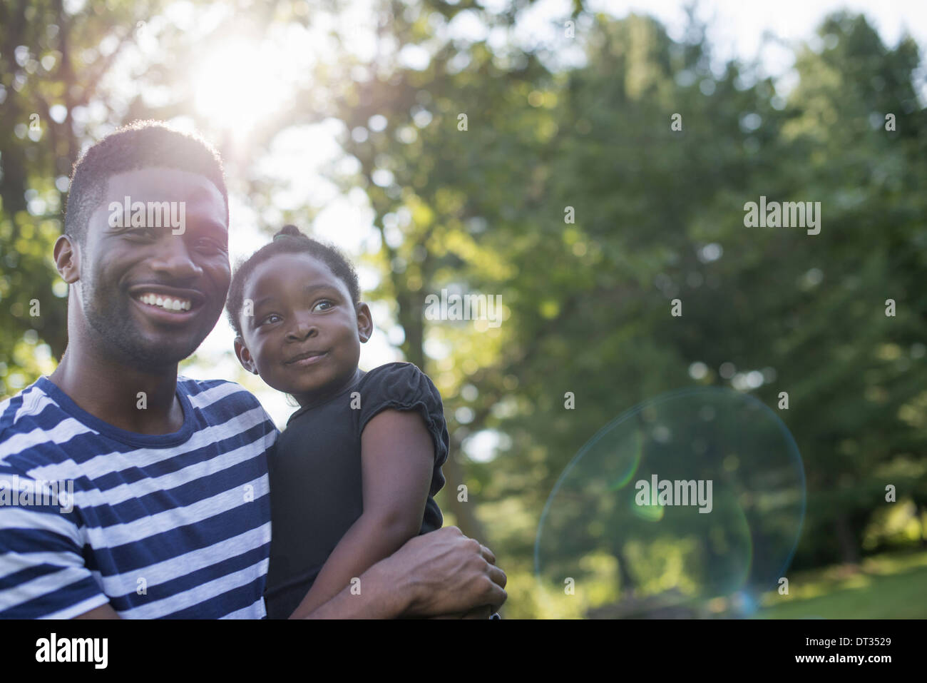 A man holding a small child in his arms in the shade of trees on a hot summer day Stock Photo