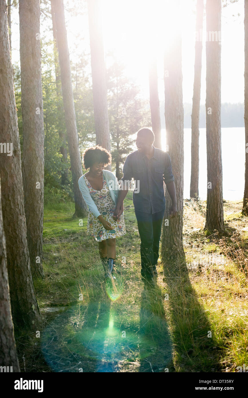 A happy couple in a shady spot in woodland in summer - Stock Image