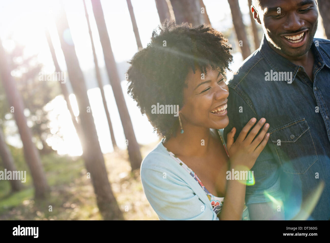 A happy couple in a shady spot in woodland in summer Hugging and holding each other - Stock Image