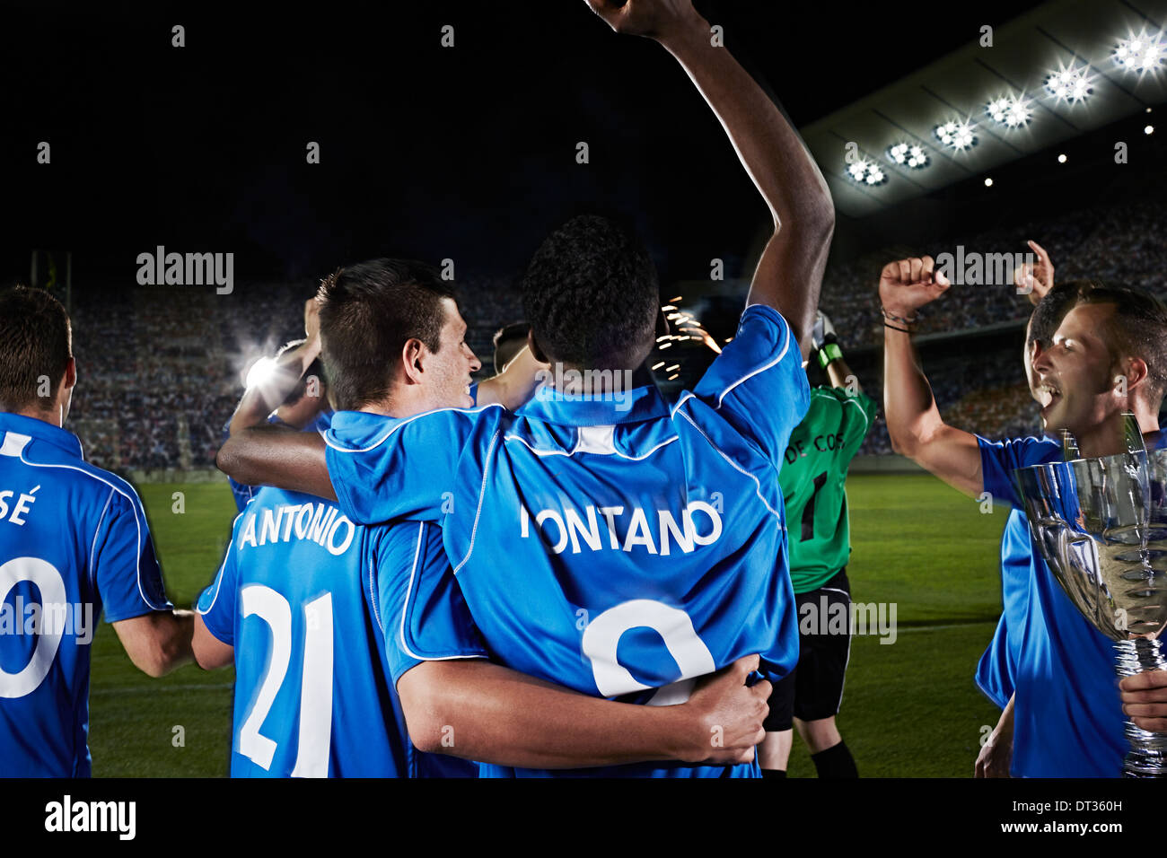 Soccer team cheering on field - Stock Image