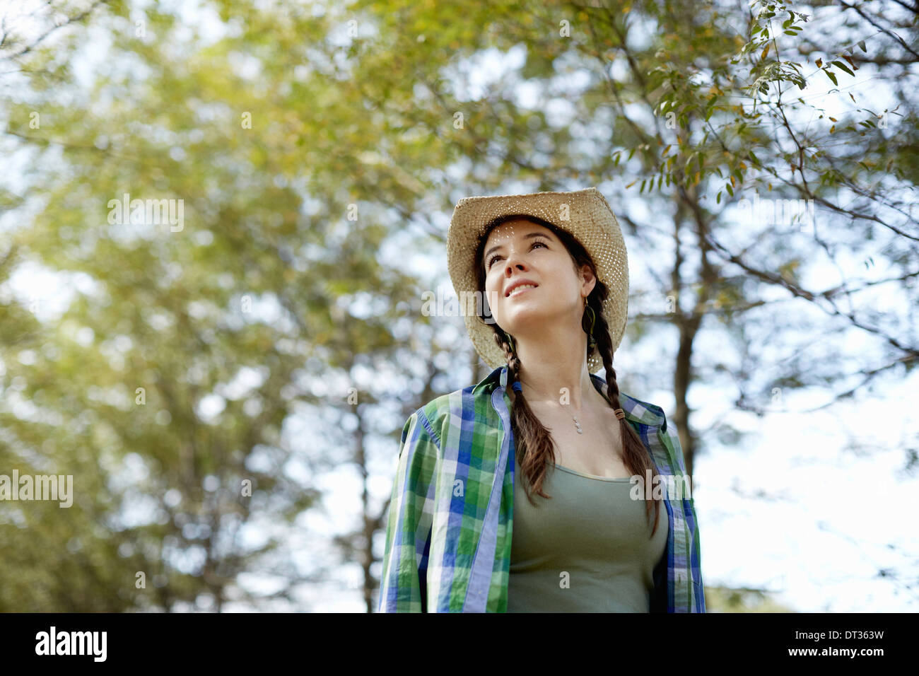 A girl in a straw hat walking in the woods - Stock Image