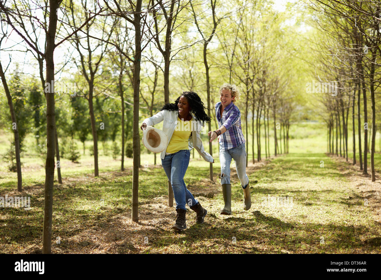 A girl stealing a young man's hat and running away with it - Stock Image