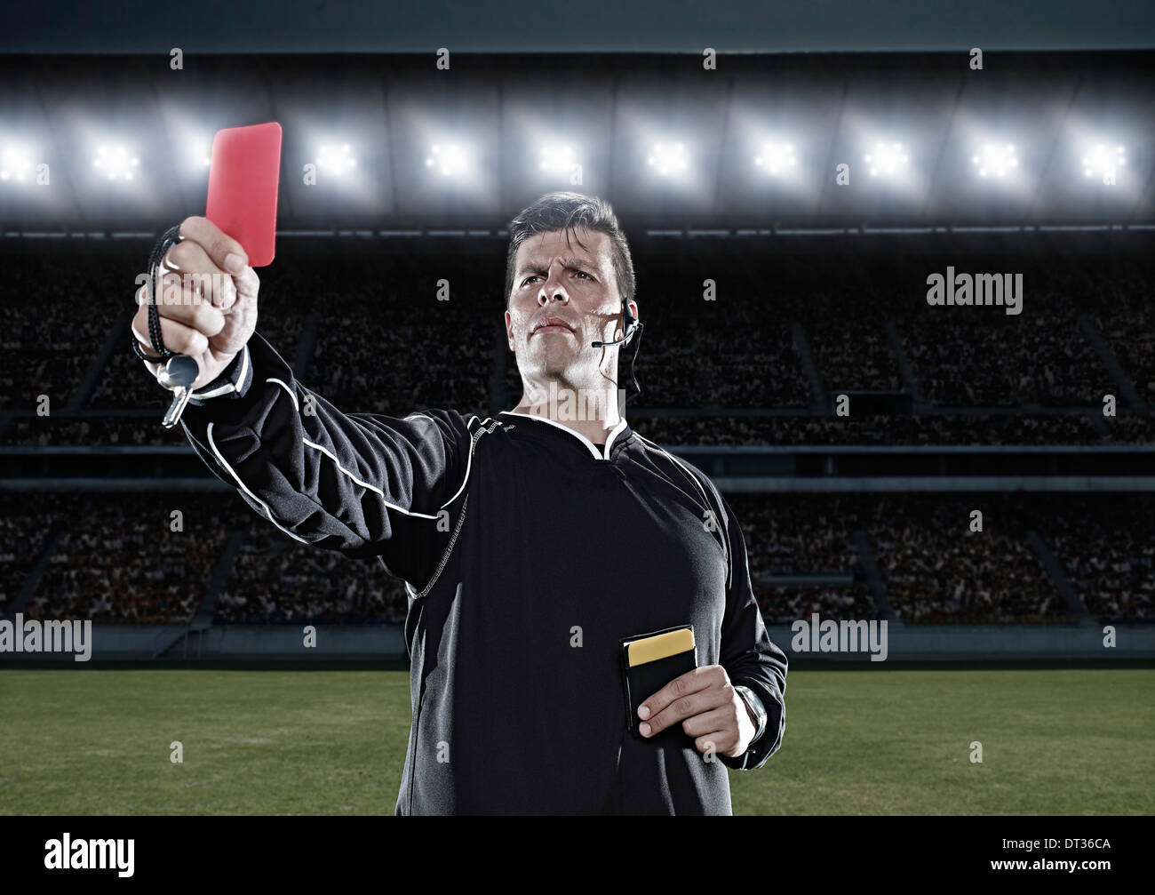 Referee flashing red card on soccer field - Stock Image