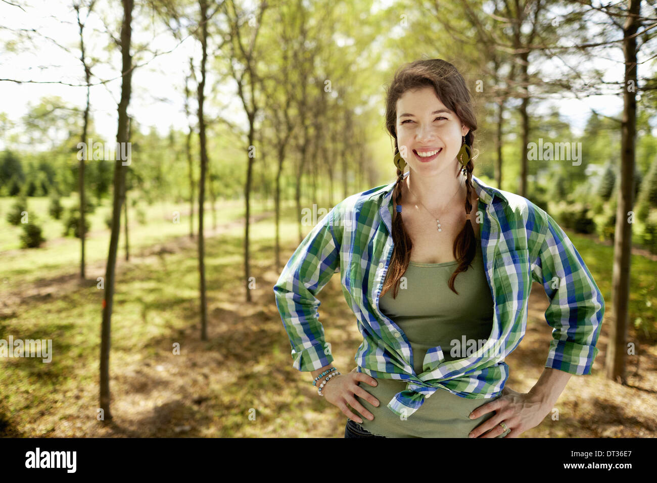 A girl in a green checked shirt with braids - Stock Image