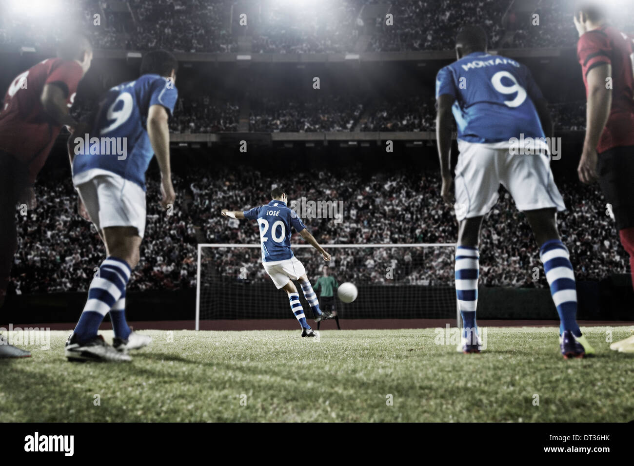 Soccer player kicking ball at goal - Stock Image
