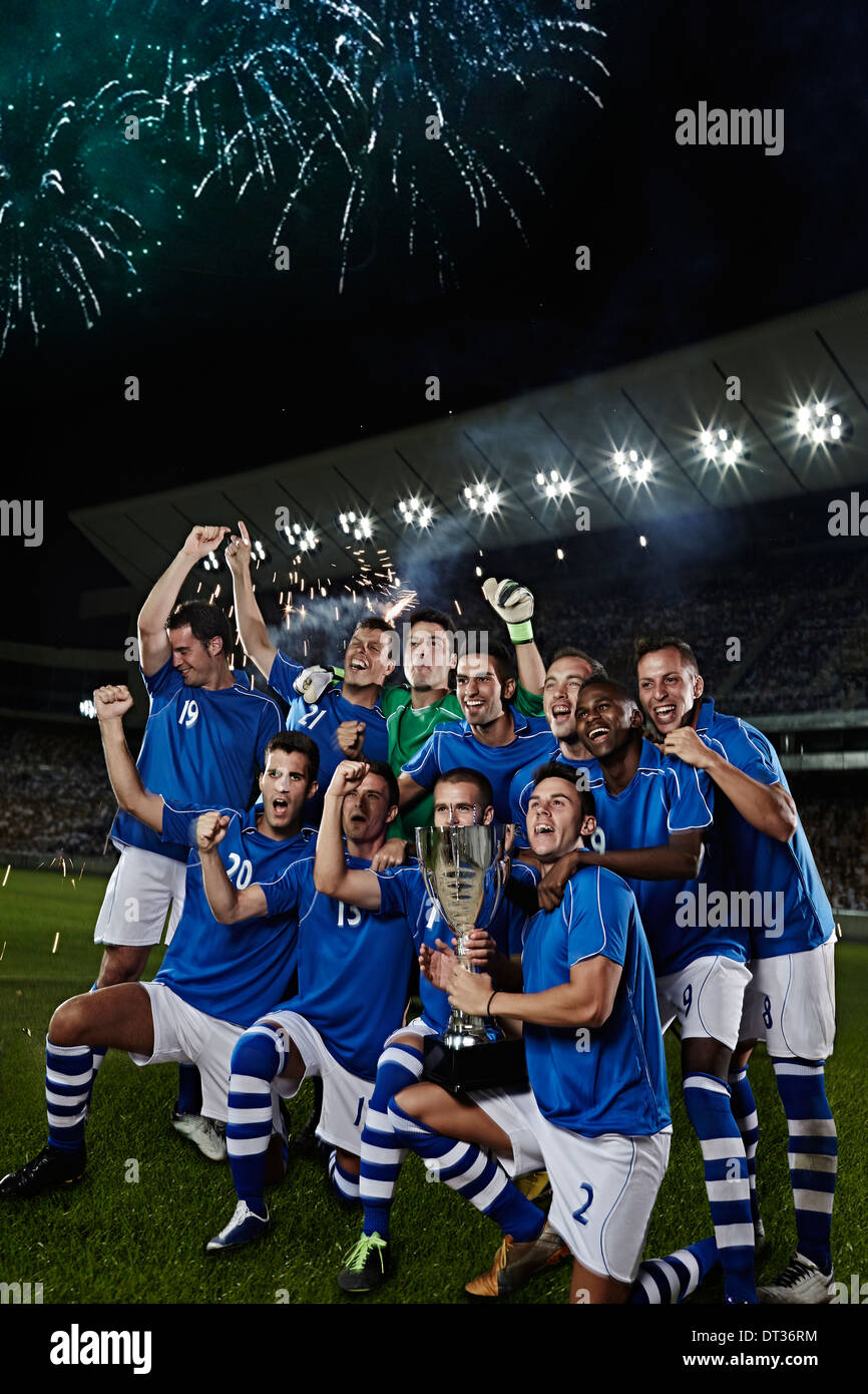 Soccer team cheering with trophy on field - Stock Image