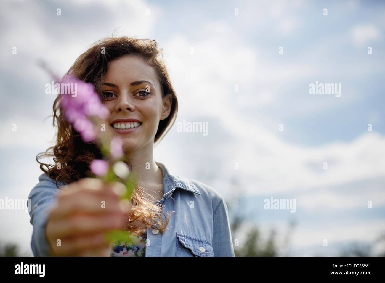 A young woman holding out a wild flower with pink petals - Stock Image