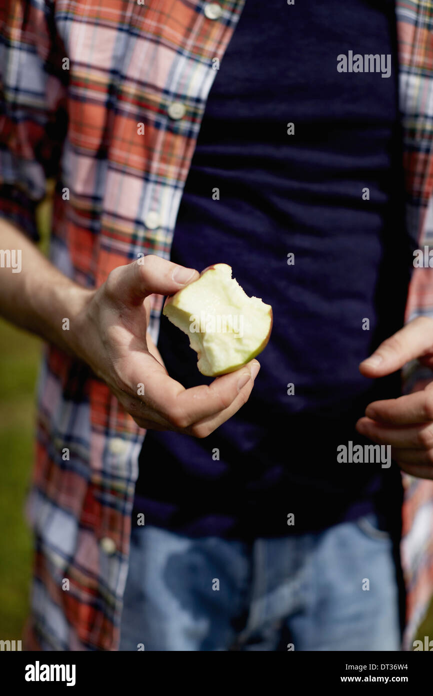 Mid section of a man wearing a plaid shirt holding a half eaten apple - Stock Image