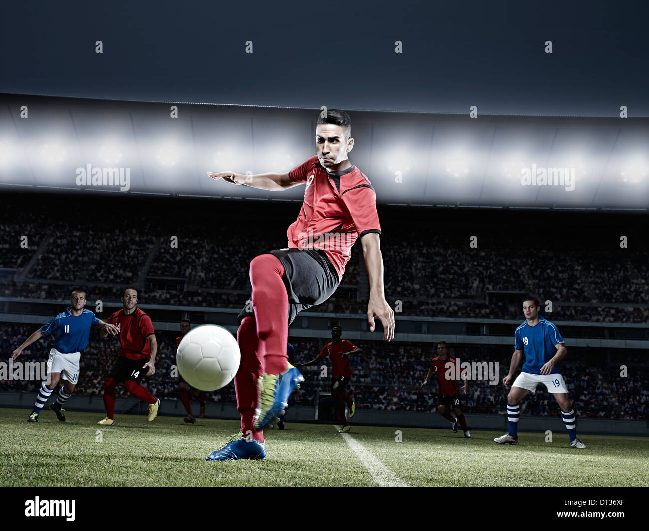 Soccer player kicking ball on field - Stock Image