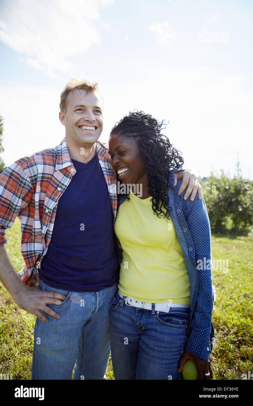 A couple a young man and woman side by side laughing - Stock Image