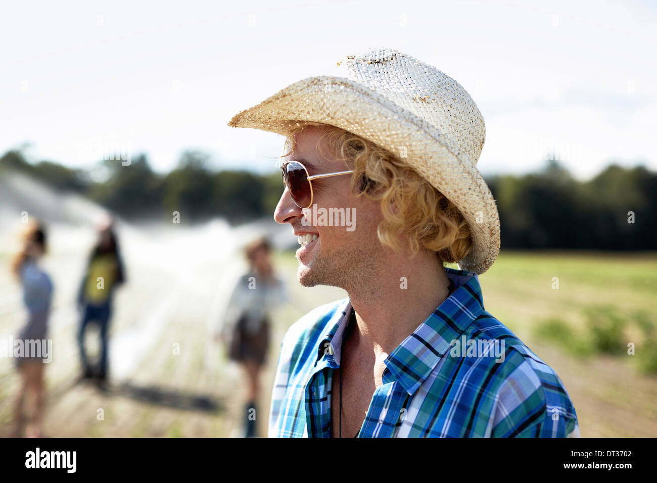 A young man in straw hat and sunglasses Irrigation sprinklers in the field Stock Photo