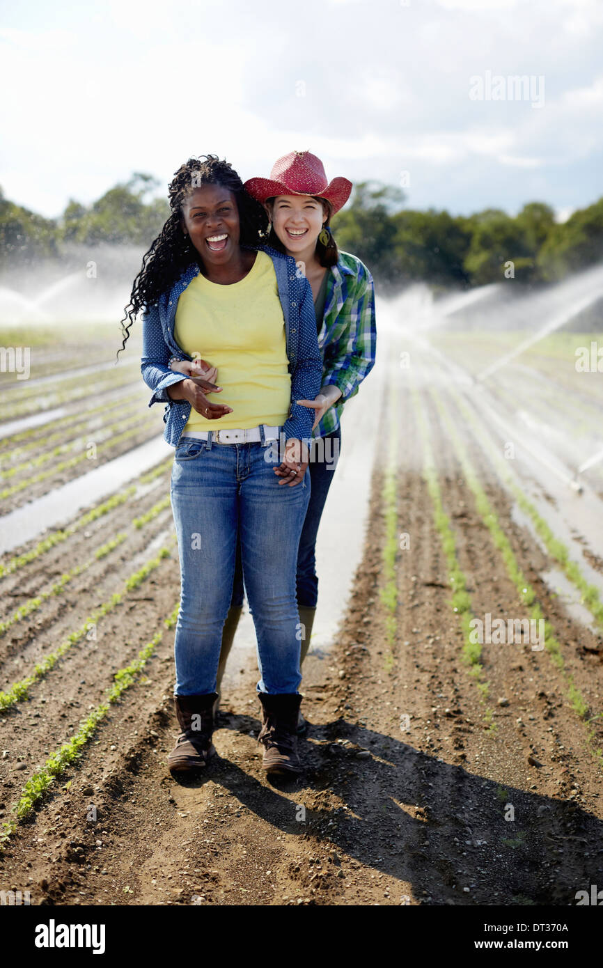 Two young women standing in a field of small seedlings with the irrigation sprinklers spraying the ground - Stock Image