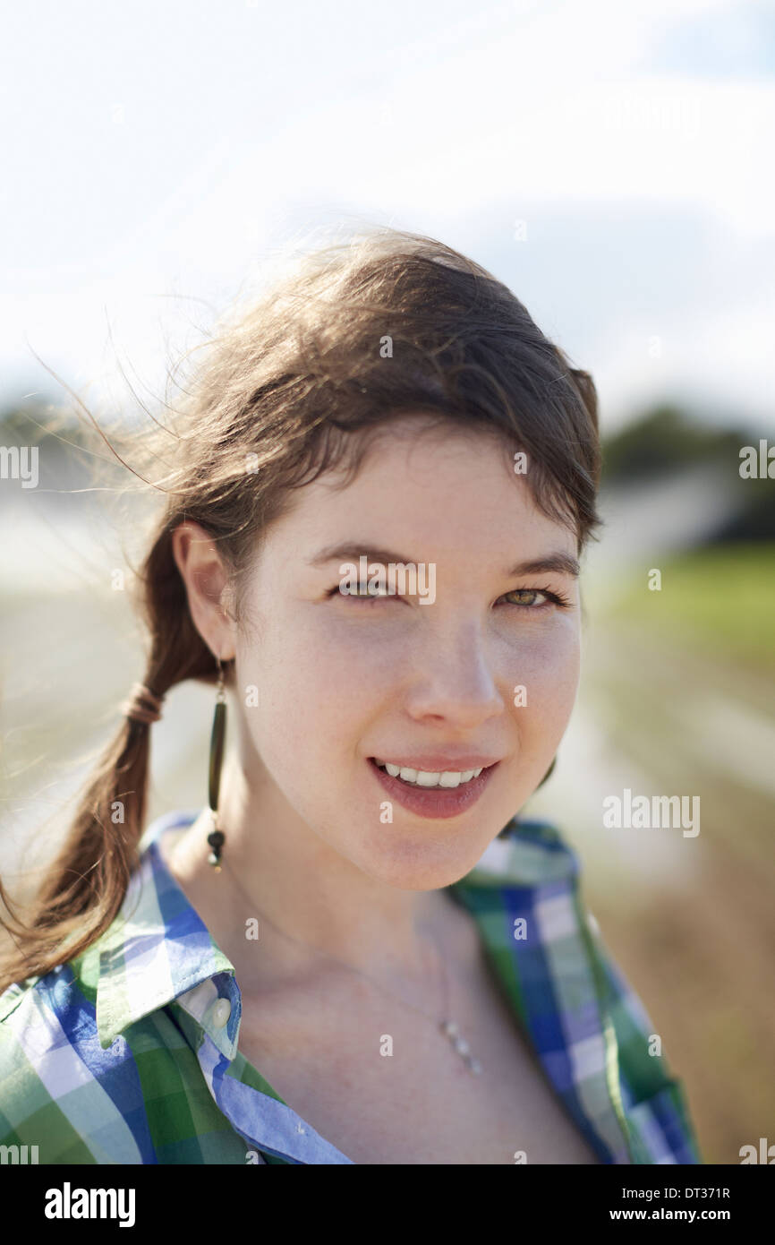 A young woman with braids green blue plaid shirt - Stock Image