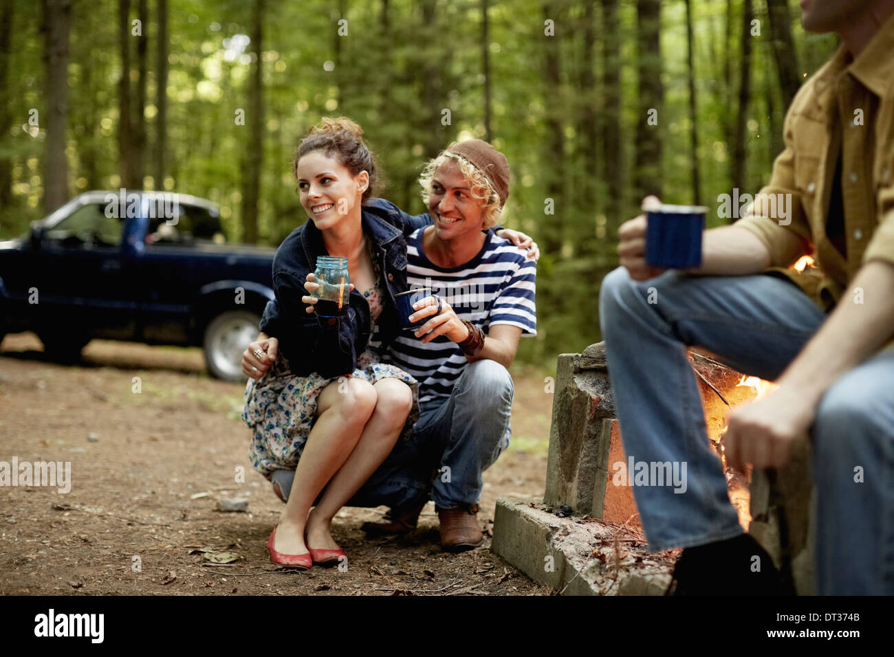 Three people sitting around a campfire at dusk - Stock Image