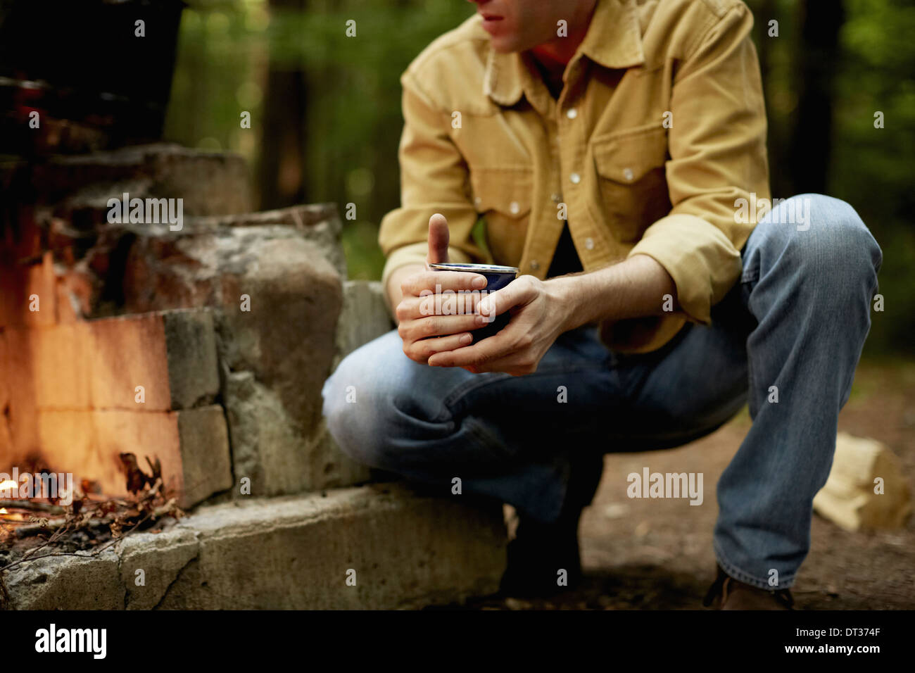 A man kneeling by a blazing camp fire - Stock Image