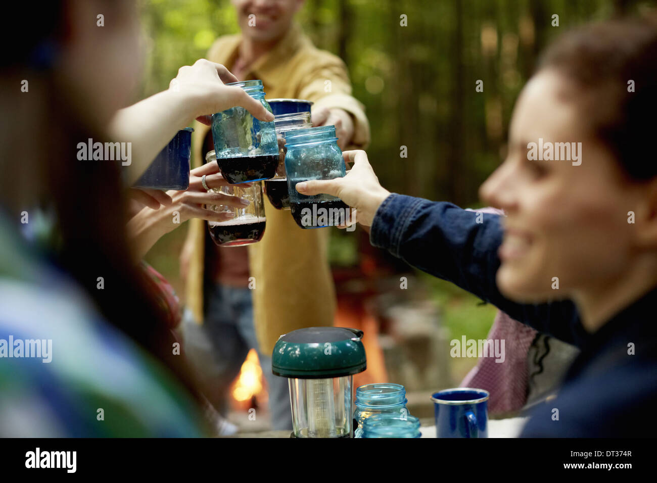 A campsite clearing in the woods People seated - Stock Image