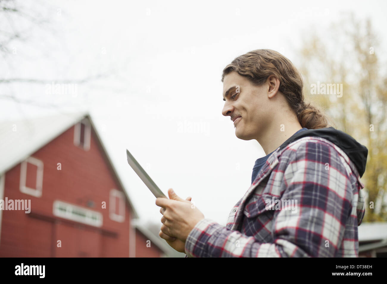 A young man using a computer tablet, a portable PC tablet device, on an organic farm. - Stock Image