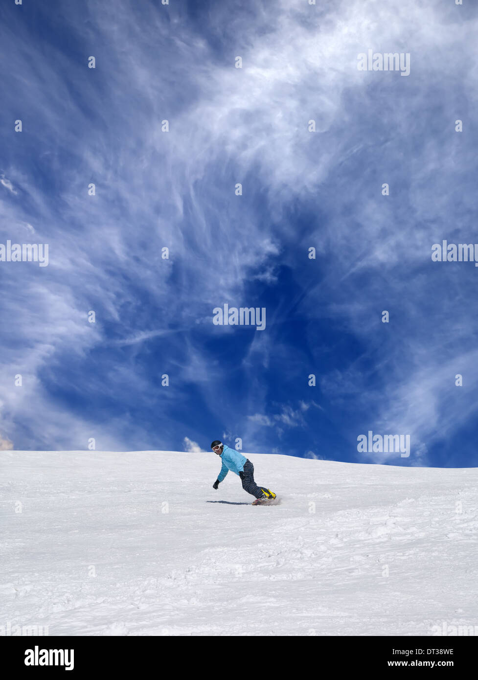 Snowboarder on off-piste ski slope and blue sky with clouds - Stock Image