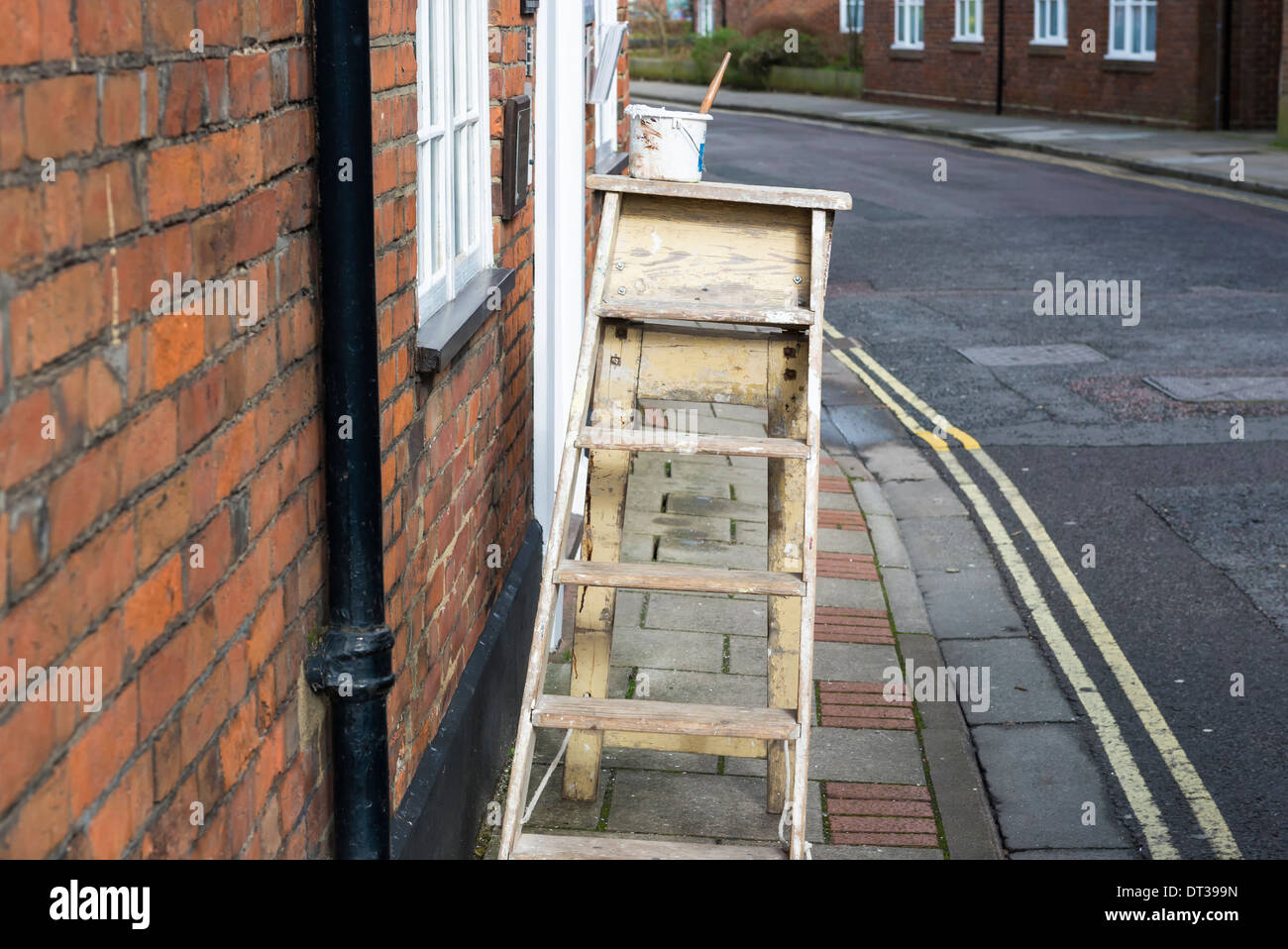 A pair of decorators steps complete with paint kettle and brush left blocking a public footpath causing a hazard for the elderly - Stock Image