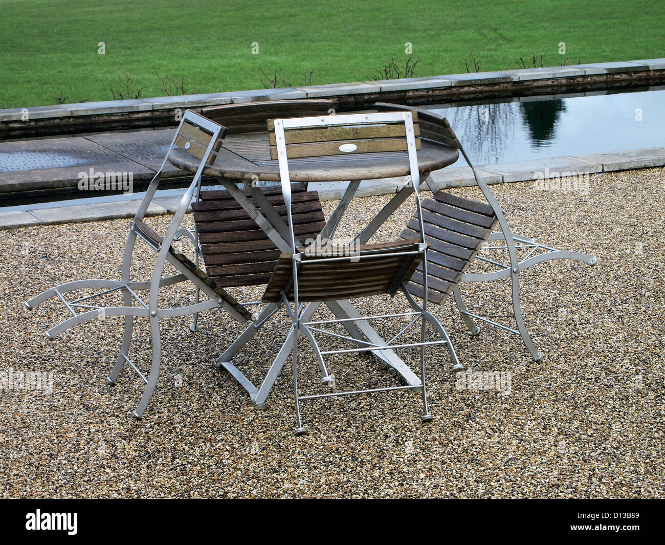 Picnic table and chairs optimistically placed outside a cafe at a public garden at the end of January on a dull wet day. - Stock Image