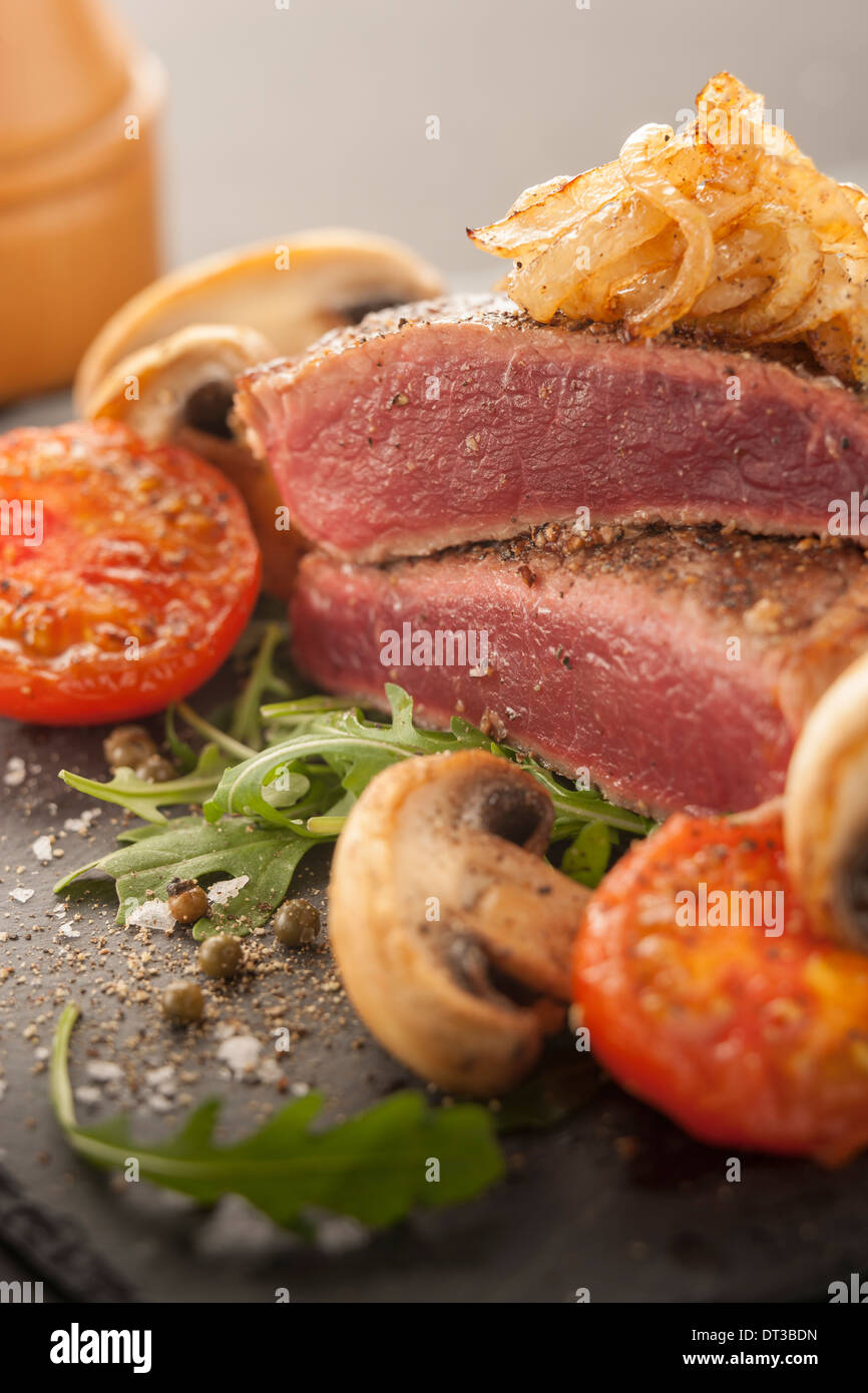 Rare steak with tomato and mushrooms Stock Photo