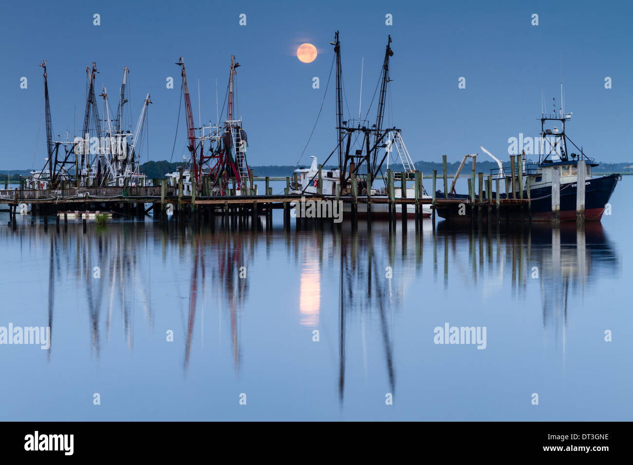 Shrimp boats at a dock with the full moon setting in the background. - Stock Image