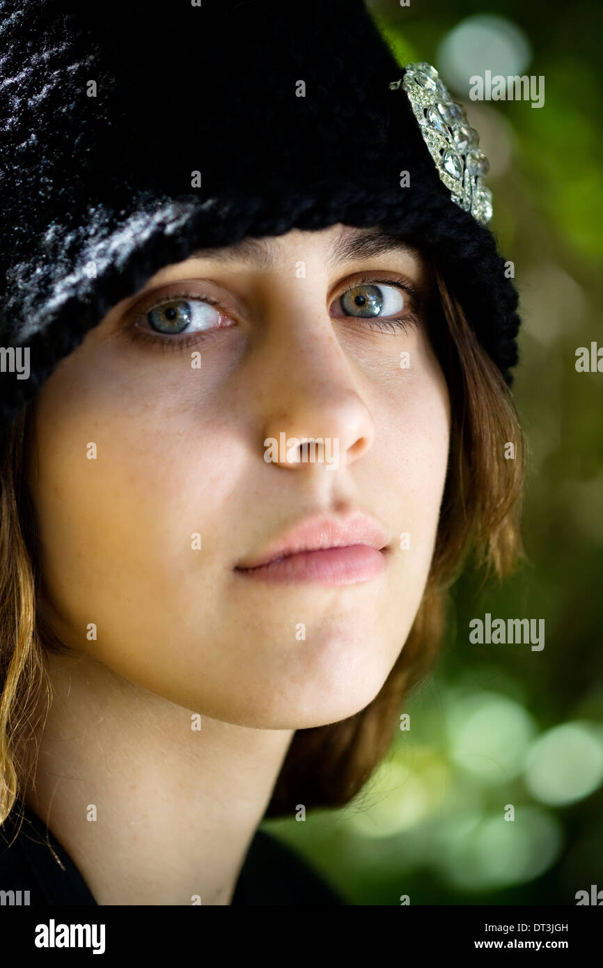 Portrait of a fair complected young woman wearing a black cloche. - Stock Image