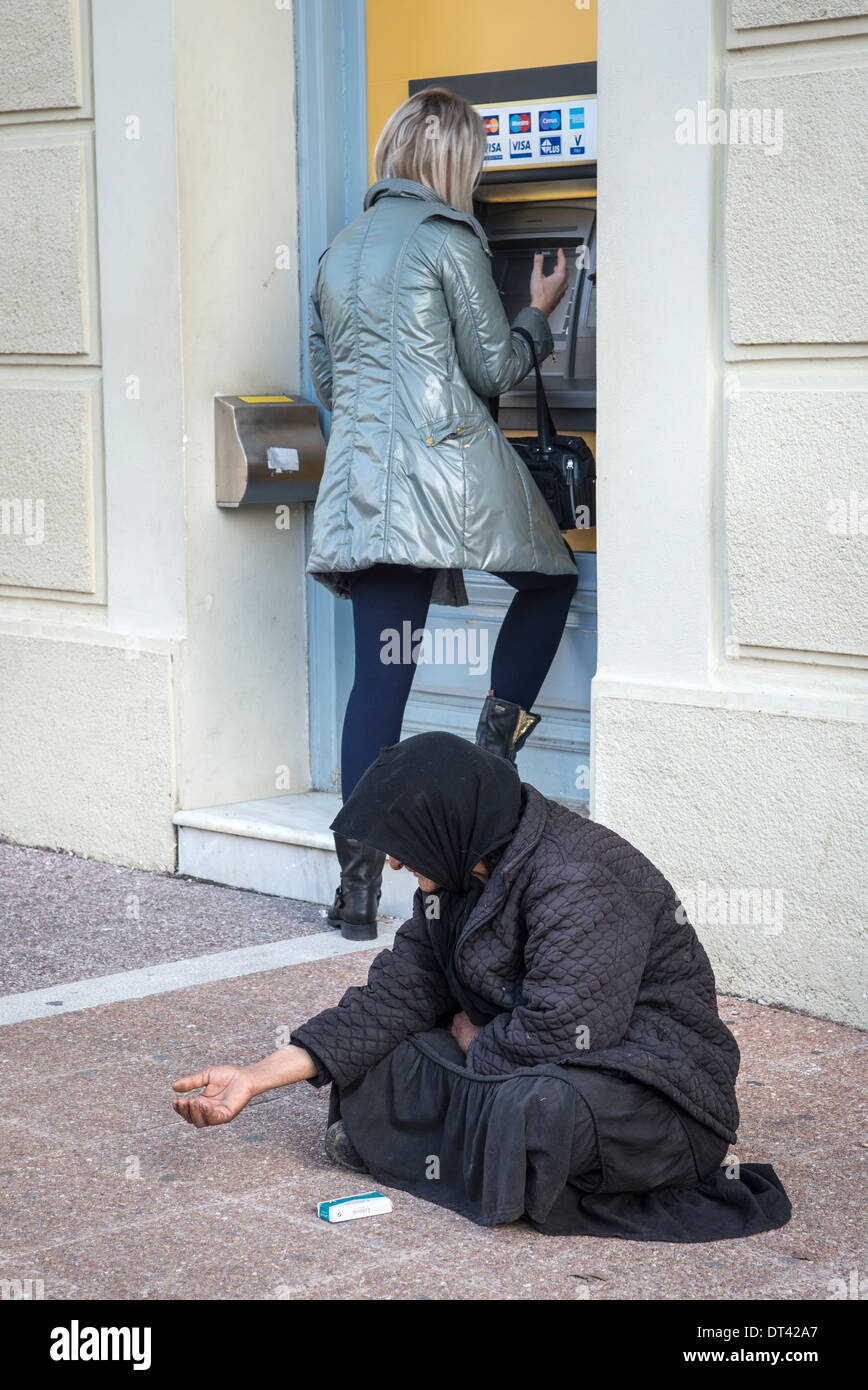 woman begging next to an ATM cash machine in the town of Kalamata, Peloponnese, Greece - Stock Image