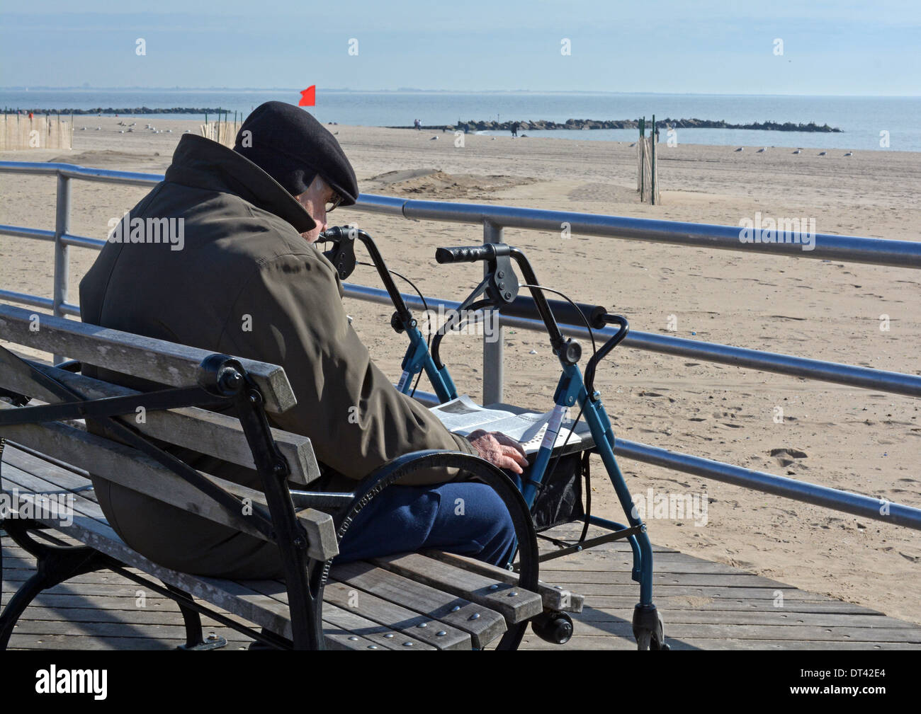 A Russian immigrant reads a magazine on a cold winter day on the boardwalk in Coney Island Brooklyn, New York - Stock Image