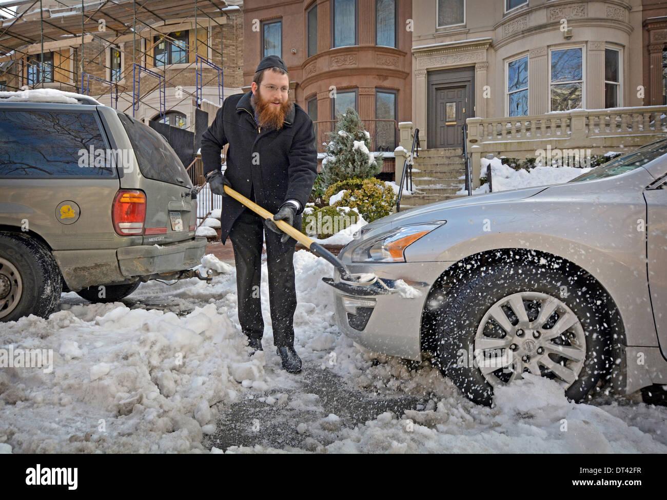 Hasidic religious Jewish rabbi shoveling snow in Crown Heights, Brooklyn, New York - Stock Image