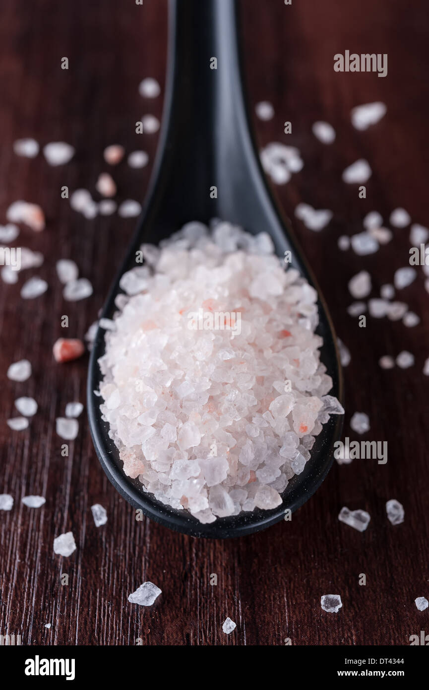 Himalayan pink salt in the black spoon - Stock Image