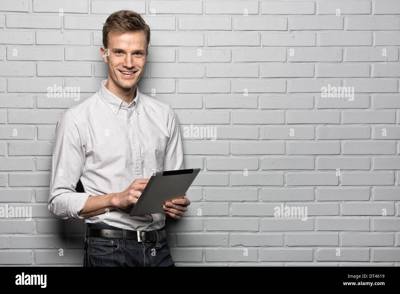 Male portrait smiling digital tablet studio brick looking camera - Stock Image
