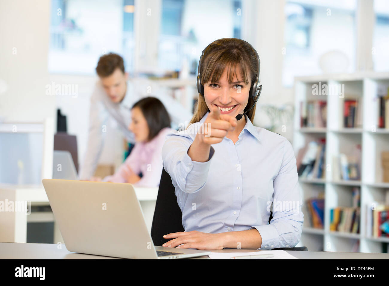 Happy business woman desk smiling point finger computer Stock Photo