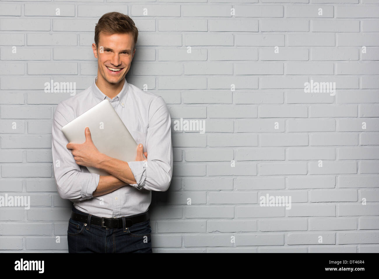Male smiling computer studio grey background looking camera - Stock Image