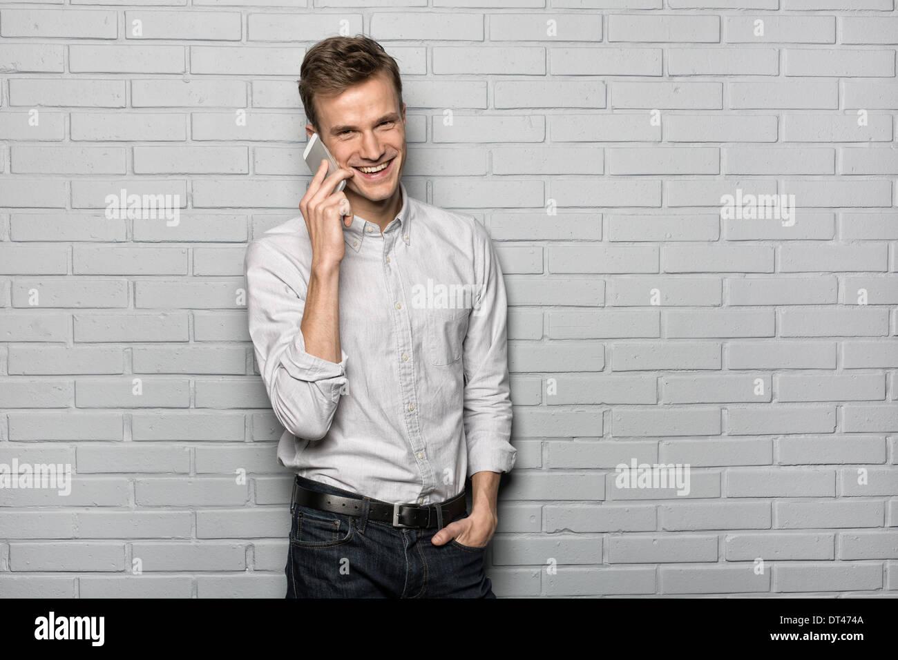 Male portrait smiling Mobile Phone studio brick looking camera - Stock Image