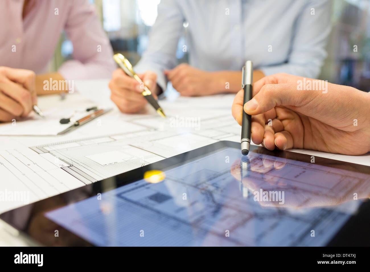 Business team desk architect man woman digital tablet blueprint construction - Stock Image