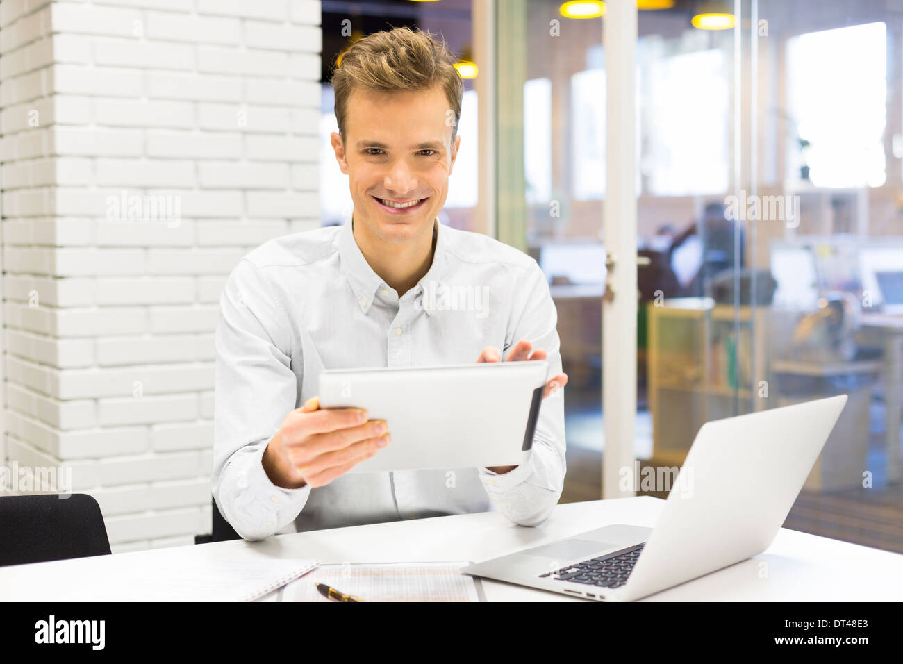 Man business tablet pc desk laptop message e-mail looking camera - Stock Image