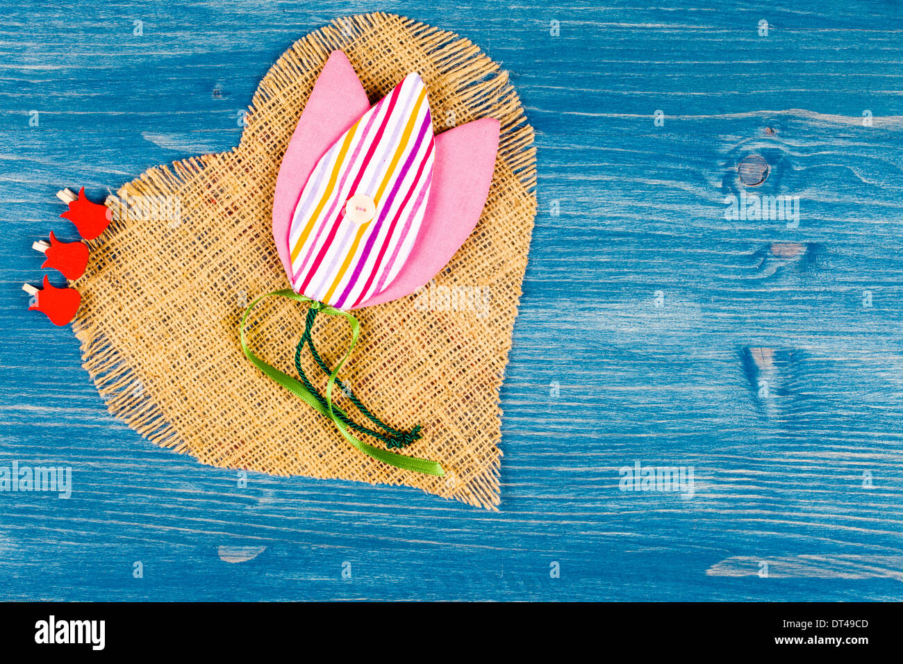 Heart made of linen on a blue background, with fabric Tulip - Stock Image