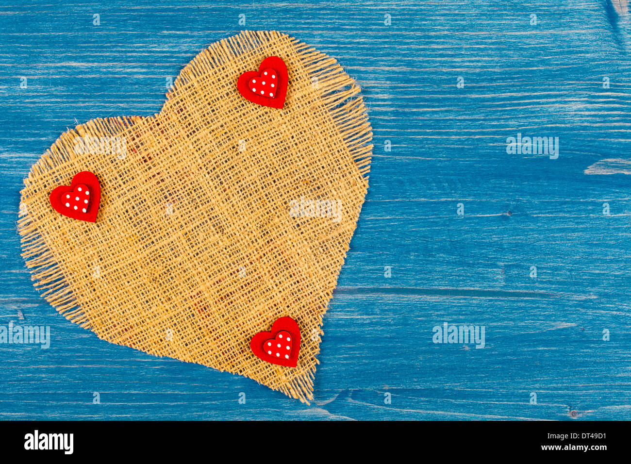 Heart made of linen on a blue background with 3 little hearts - Stock Image