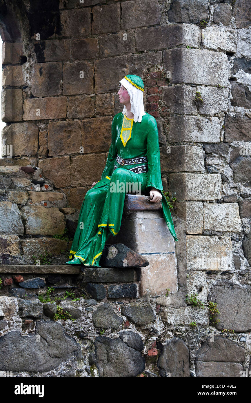 A historical model of a woman sits in an alcove of Carrickfergus Castle, a Norman castle in Northern Ireland, - Stock Image