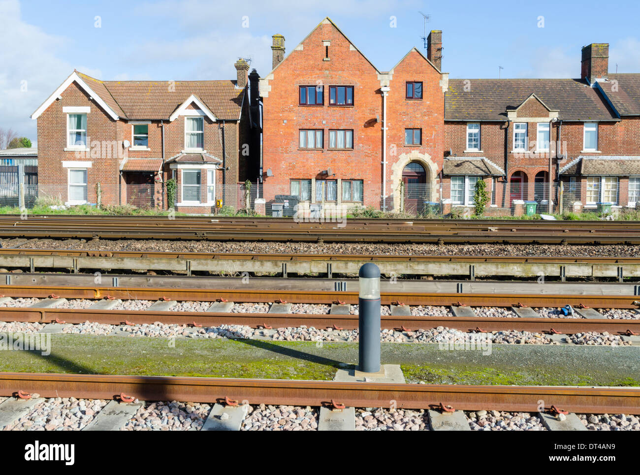 Railway track going past housing in an urban area in the UK. - Stock Image
