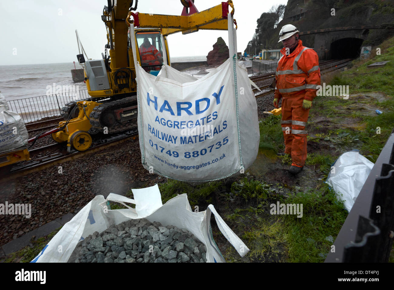 Dawlish, UK. 8th Feb, 2014. Aggregate is loaded onto a rail carriage to begin repairing the severed rail  line at Dawlish in Devon England after the severe storms. Credit Paul Glendell 8th Feb 2014 - Stock Image