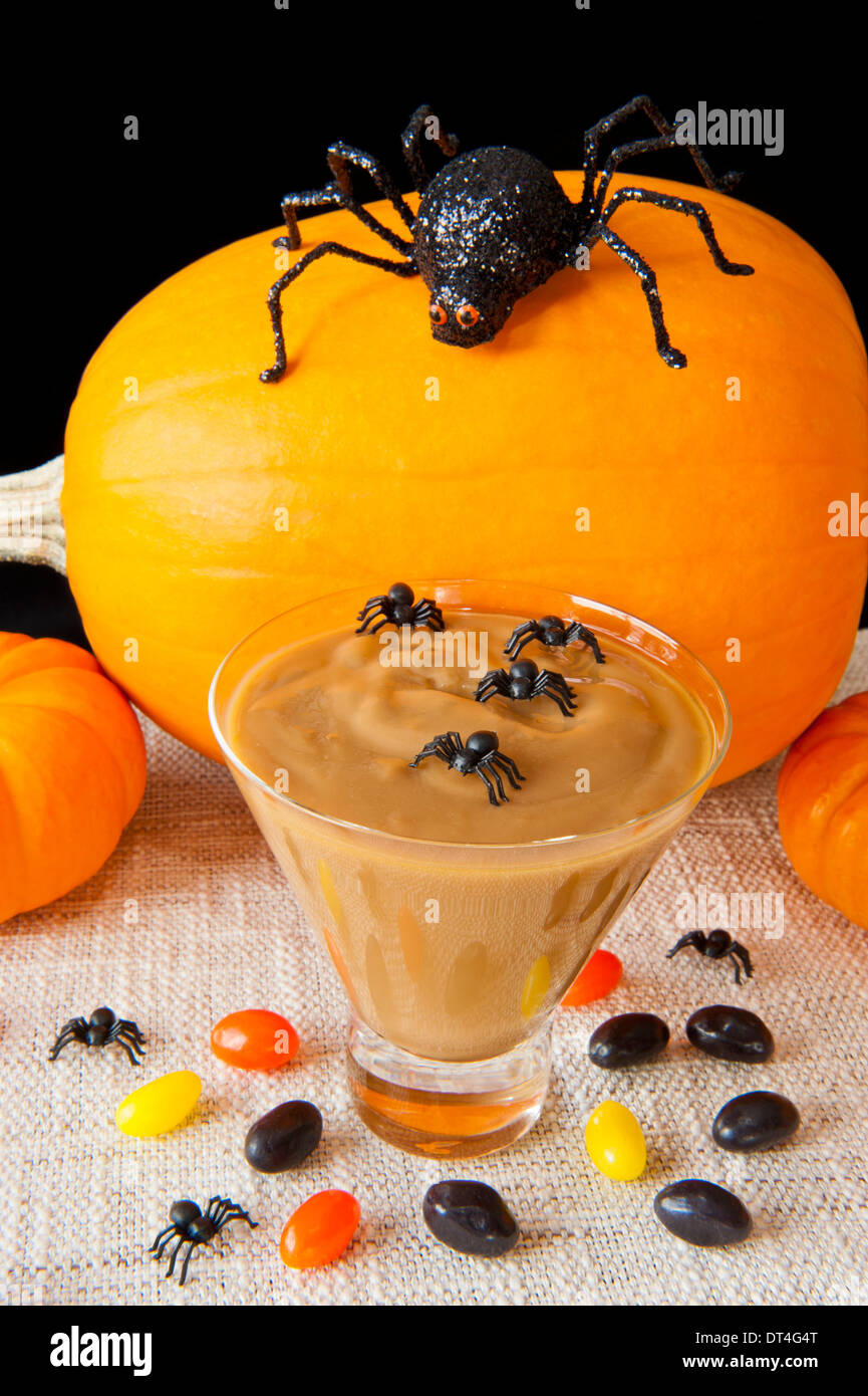 Caramel pudding with Halloween spiders, jelly beans and pumpkins - Stock Image