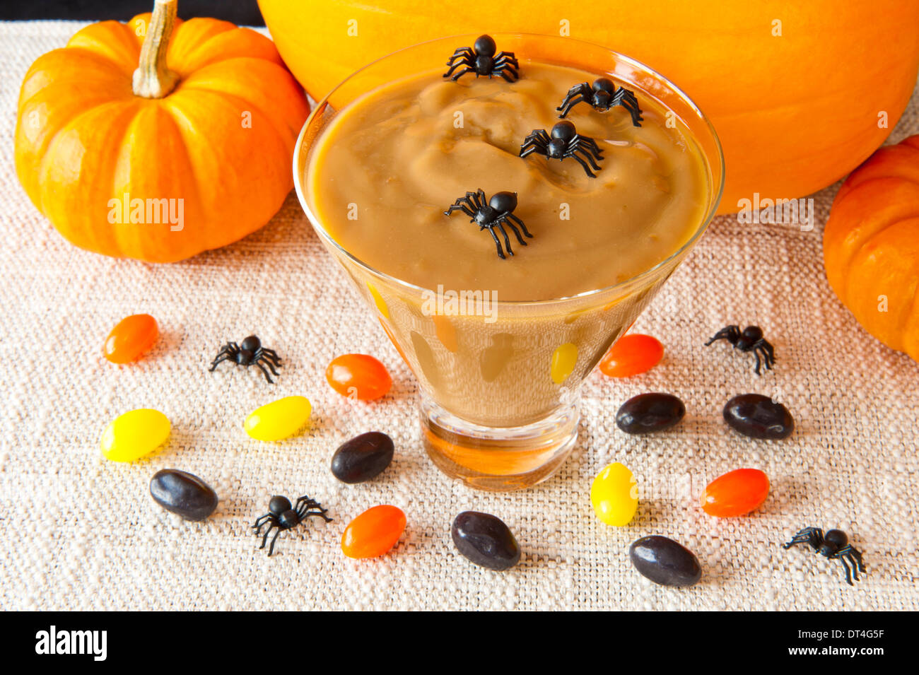 Spiders and Jellybeans decorate butterscotch pudding for Halloween - Stock Image
