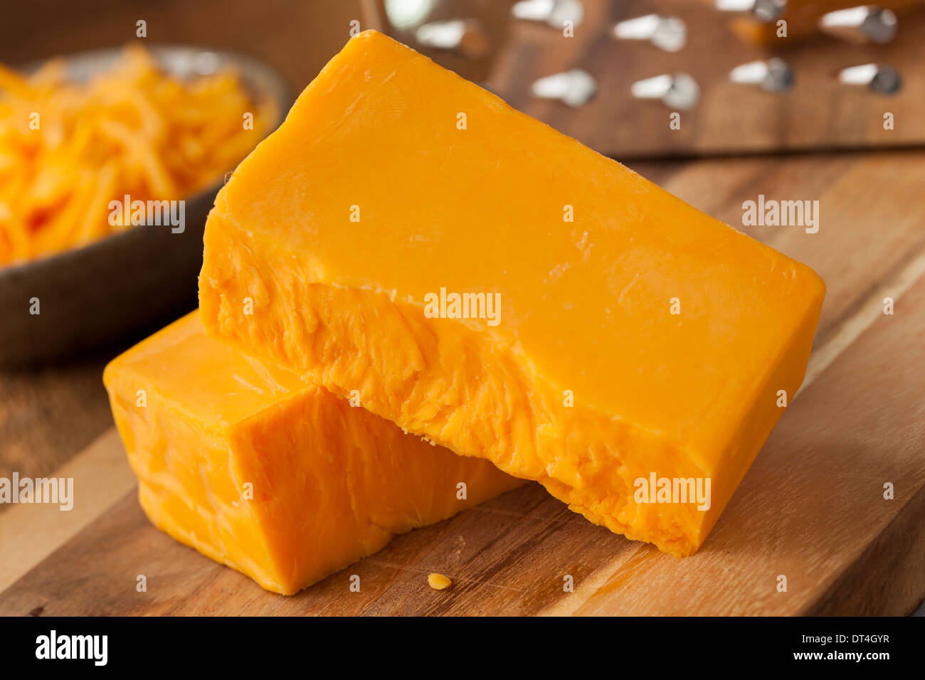 Organic Sharp Cheddar Cheese on a Cutting Board - Stock Image